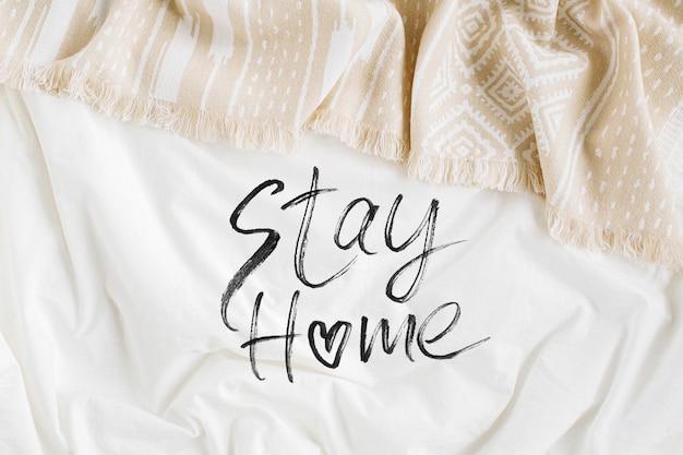 Оставайся дома, на карантин. белое постельное белье с тёплым пледом. уютный фон с копией пространства. скандинавский стиль. плоская планировка, вид сверху