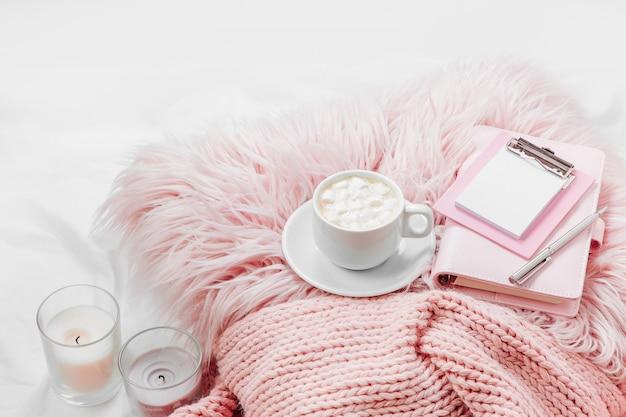 Оставайся дома, на карантин. работаю из дома. чашка кофе на розовой подушке с блокнотом и одеяло на кровати.