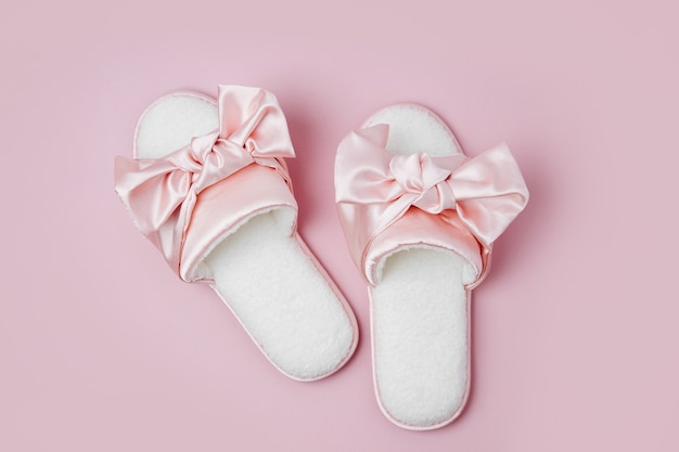 Stay home, quarantine. working from home. beautiful female slippers with bow on a pink background. flat lay, top view