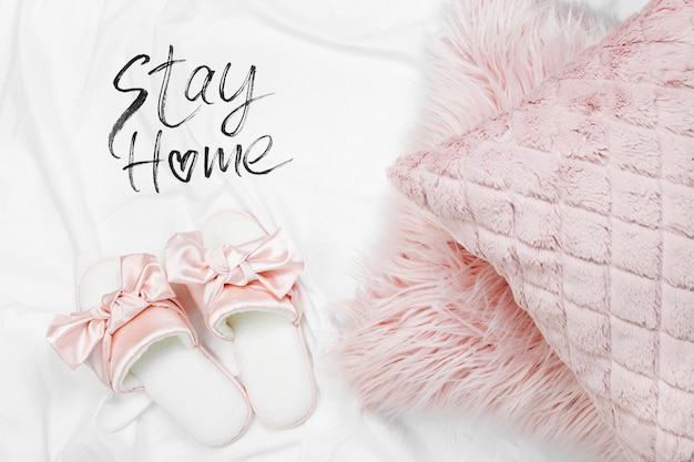 Stay home, quarantine. working from home. bedding with a stylish pink pillows and slippers. copy space. flat lay, top view