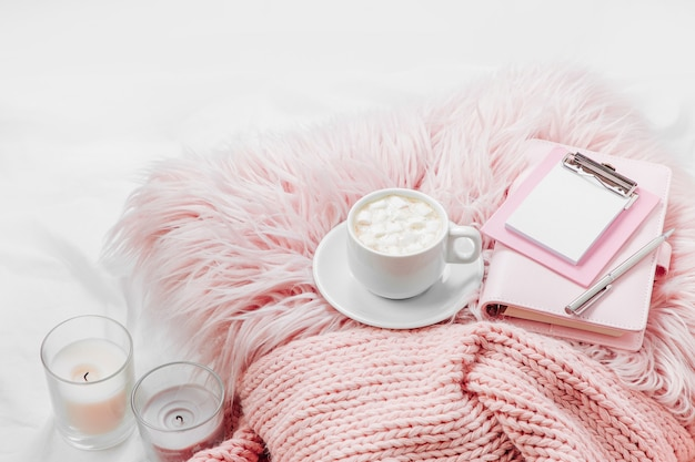 Stay home, quarantine. working from home. a cup of coffee on a pink pillow with notebook and a blanket on the bed.