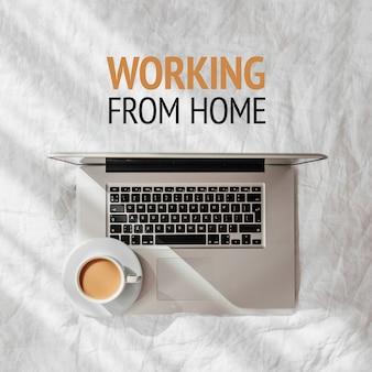 Оставайся дома, на карантин. работаю из дома. ноутбук и чашка кофе на белой кровати. работа дома концепции.