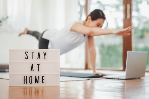 Оставайтесь дома знак лайтбокс с женщиной, практикующей йогу, упражнения на растяжку через ноутбук в гостиной дома в фоновом режиме. самоизоляция и тренировки дома во время covid-19