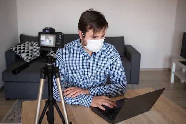 家にいて安全に。コロナウイルスの検疫で家にいる間、家でビデオを記録するビジネスブロガー