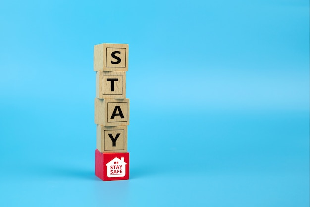 家にいて木のおもちゃのブロックに安全なアイコンを置いてください。コロナウイルスやcovid-19感染の健康と医療の予防の概念。