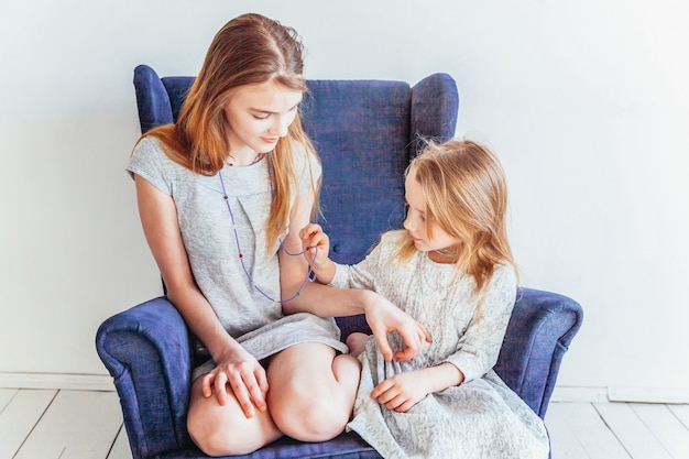 Stay home stay safe. two happy kids sitting on cozy blue chair relaxing playing in white living room indoors. little girl playing with teenage girl showing her love care. sisters having fun at home.