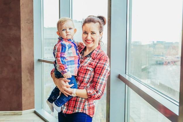 家にいる。若い母親が彼女の子供を保持しています。女性と幼児の女の子が室内の窓の近くの白い寝室でリラックス。自宅で幸せな家族。若いお母さんが娘と遊ぶ。
