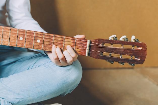 안전을 유지하십시오. 젊은 여자 집에 앉아 기타 연주, 손을 닫습니다. 노래를 연주하고 음악을 배우는 십 대 소녀. 취미 생활은 악기 레저 교육 개념을 휴식.