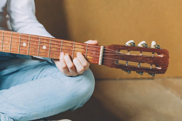 Stay home stay safe. young woman sitting at home and playing guitar, hands close up. teen girl learning to play song and writing music. hobby lifestyle relax instrument leisure education concept.