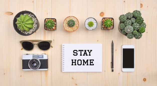 Stay home text with flat lay of accessories on wooden desk