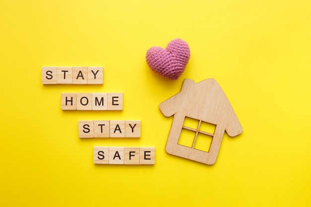 Stay home text with wooden house with knitted heart on yellow background. quarantine concept, covid-19 virus protection. top view, flat lay.