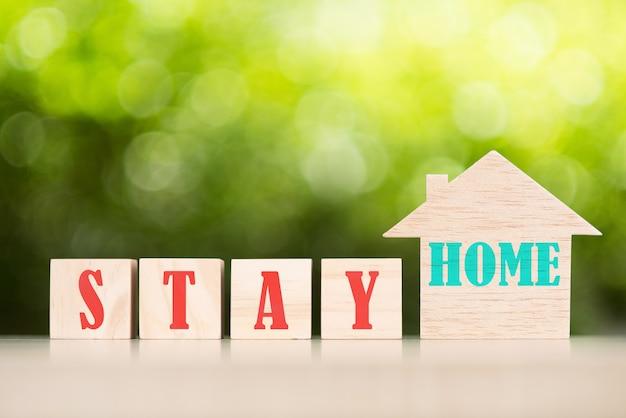 Оставайся дома текст с деревянным игрушечным домиком