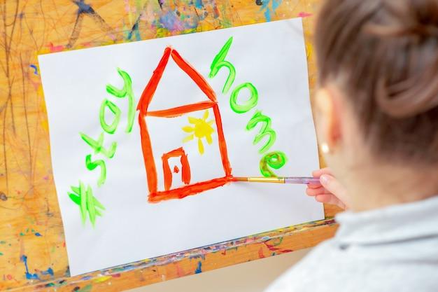 Ребенок рисует красный дом со словами stay home