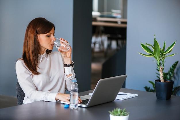水分補給をしてください。女性はオフィスで水を飲む
