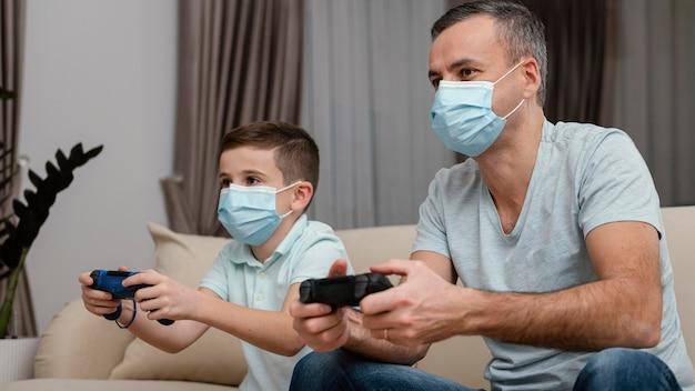 Оставайтесь дома мужчина и ребенок, играя в видеоигры