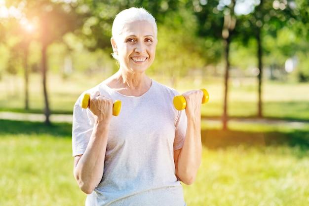 긍정적으로 생각해. 아령을 들고 기쁘게 웃는 은퇴 한 여자