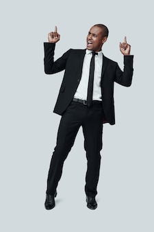 긍정적으로 생각해! 회색 배경에 서 있는 동안 얼굴을 만들고 몸짓을 하는 정장을 입은 잘생긴 젊은 아프리카 남자의 전체 길이