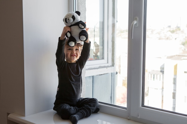 Stay positive at home. happy and cheerful a child sits on a windowsill and plays with a panda teddy bear