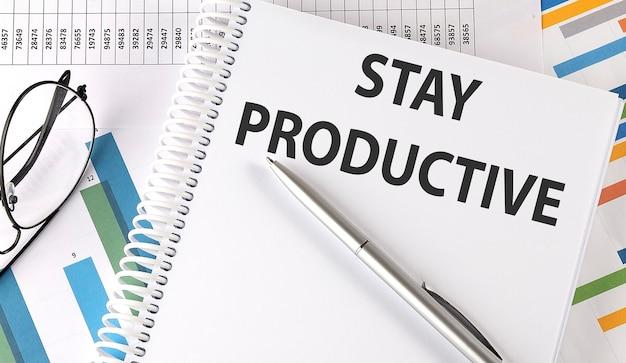 Оставайтесь продуктивным ручка и очки на графике, бизнес-концепция