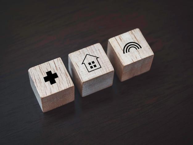 안전한 개념을 유지하십시오. 나무 배경에 있는 나무 블록에 있는 집, 건강 관리, 무지개 아이콘. 집에 머물면서 코비드-19, 코로나바이러스 전염병 예방을 위한 긍정적인 소셜 미디어 캠페인을 생각하십시오.