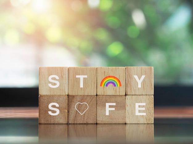 안전한 개념을 유지하십시오. 나무 블록에 무지개와 하트 아이콘이 있는