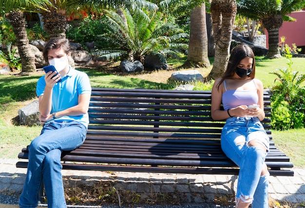 おげんきで。社会的距離と顔の保護マスクを身に着けているスマートフォンを使用して2人の若者の男性と女性