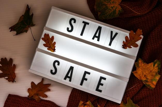 안전히 계세요. 흰색 조명 상자에 있는 텍스트, 스웨터 배경, 말린 잎 가을 장식. 코로나바이러스 장치. 사회적 거리두기. 전염병에 대한 보호. 아늑한 집