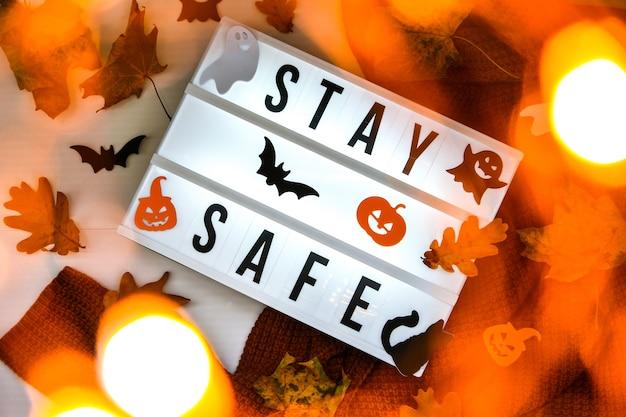 안전히 계세요. 흰색 조명 상자의 텍스트, 스웨터 배경, 말린 잎 할로윈 가을 장식. 코로나바이러스 장치. 사회적 거리두기. 전염병에 대한 보호. 아늑한 집