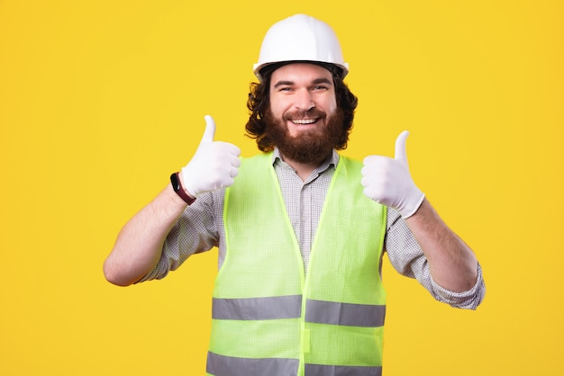 헬멧을 안전하게 착용하십시오. 엄지 손가락을 보여주는 조끼를 입고 웃는 건축가