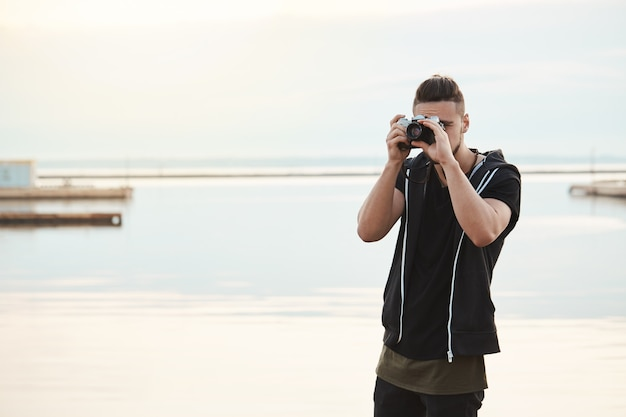 Stay where you are, this photo is amazing. portrait of creative good-looking freelance photographer looking through camera while taking shots of nature and people, standing near seashore