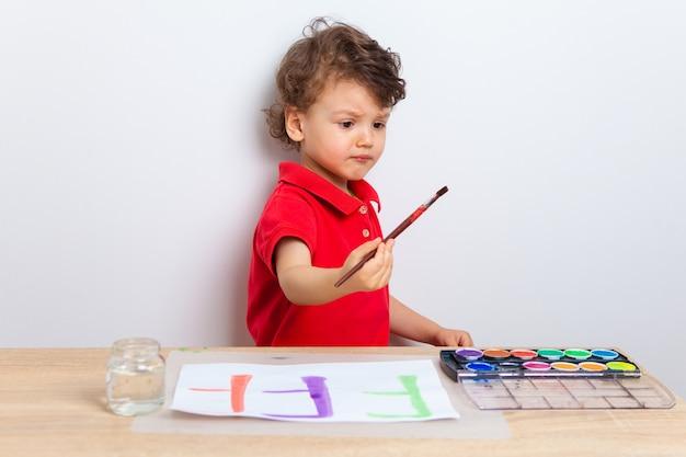 집에서 아이와 함께 있으십시오. 코로나 바이러스 검역 중 미취학 아동과의 관계. 아이는 테이블에 앉아서 페인트로 브러시로 그립니다.