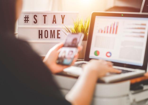 Лайтбокс с текстовым хэштегом #stayhome, светящимся в свете и размытой женщиной, работающей дома. офисный работник на карантине. работа на дому, чтобы избежать вирусных заболеваний. концепция фрилансера или удаленного работника.