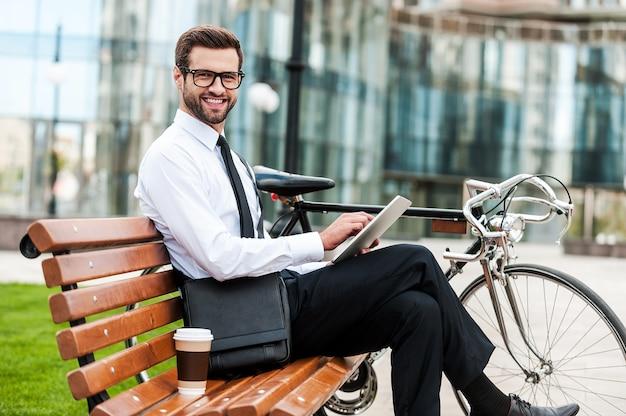 新しいテクノロジーを先取りします。彼の自転車の近くのベンチに座ってデジタルタブレットを保持し、カメラを見ている笑顔の青年実業家の側面図