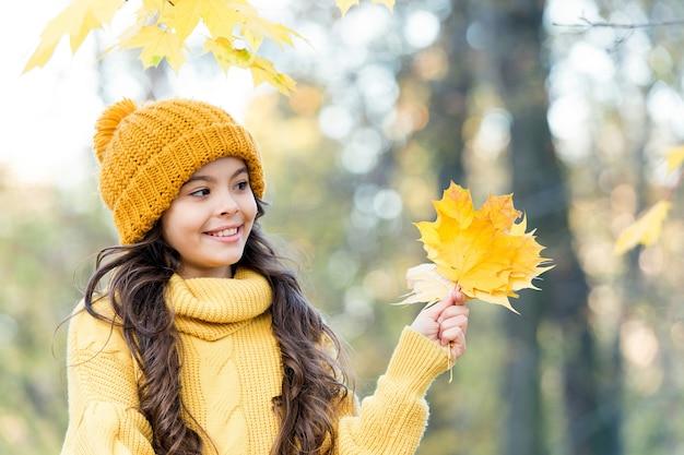 계절에 관계없이 아름다운 모습을 유지합니다. 아이가 잎을 잡아. 아이 옷 패션. 뷰티 스타일. 행복 한 소녀가 자연에서 휴식. 작은 소녀는 니트 모자와 스웨터를 입는다. 아이는 숲에서 가을 날씨를 즐길 수 있습니다.
