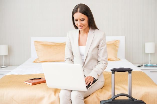 Оставайтесь на связи в любое время. красивая молодая деловая женщина в костюме работает на ноутбуке и улыбается, сидя на кровати в гостиничном номере