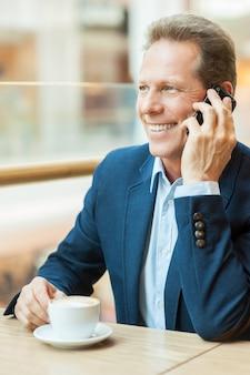 Оставаться на связи. уверенный зрелый мужчина в формальной одежде пьет кофе и разговаривает по мобильному телефону, сидя в ресторане