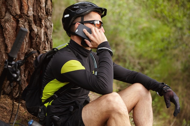 Staying connected. cropped shot of handsome young european biker wearing helmet and eyeglasses talking on mobile phone