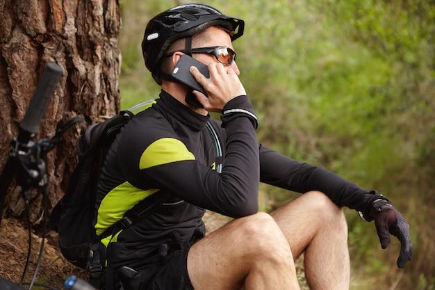 接続を維持します。ヘルメットと携帯電話で話している眼鏡を身に着けているハンサムな若いヨーロッパのバイカーのショットをトリミング