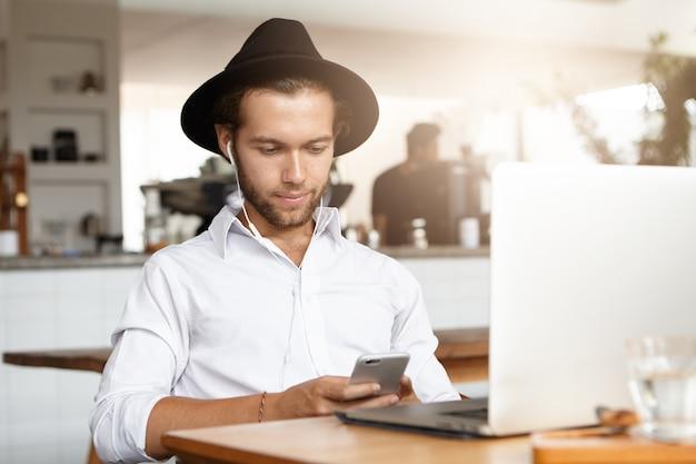 Оставаться на связи. красивый молодой человек с помощью смартфона, сидя в кафе перед ноутбуком в наушниках, ожидая своего обеда