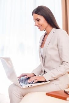 Оставаться на связи. вид сбоку красивой молодой бизнес-леди в костюме, работающей на ноутбуке и улыбающейся, сидя на кровати
