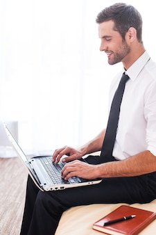 Оставаться на связи. вид сбоку красивого молодого человека в рубашке и галстуке, работающего на ноутбуке и улыбающегося, сидя на кровати