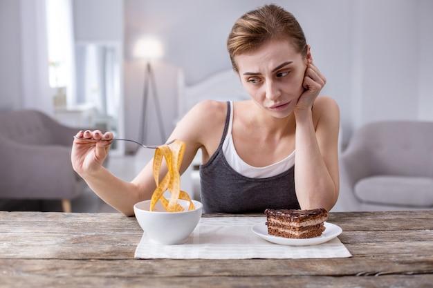 Оставаться в форме. приятная молодая женщина плохо себя чувствует, желая кусок торта