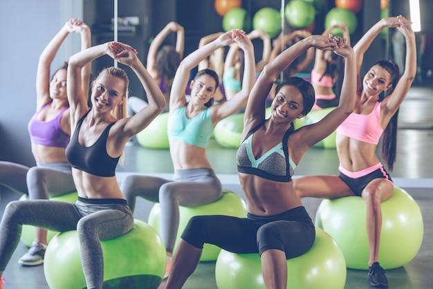 Оставаться в форме. молодые красивые женщины в спортивной одежде с идеальными телами делают растяжку и с улыбкой смотрят в камеру, сидя на фитнес-мячах в тренажерном зале