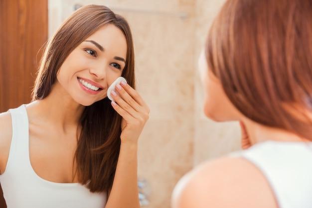 新鮮で清潔な状態を保ちます。スポンジで顔に触れ、鏡の前に立って笑っている美しい若い女性