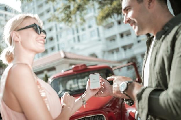 계속 웃기다. 웃고 있는 남편과 아내는 스마트폰에서 검색 요청에 대해 농담으로 서로를 바라보고 있습니다.