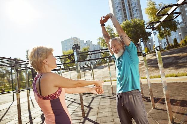 Оставаясь здоровой, активная зрелая семейная пара в спортивной одежде вместе разогревается в тренажерном зале на открытом воздухе в