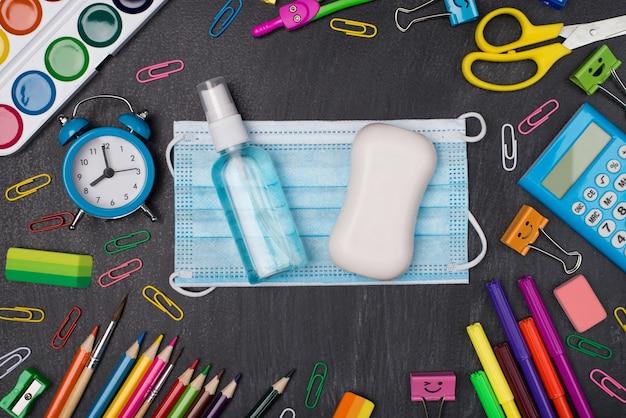 Сохранение здоровой и образованной концепции. фотография красочных канцелярских принадлежностей с мылом-маской и дезинфицирующим средством для рук в центре, изолированном на доске