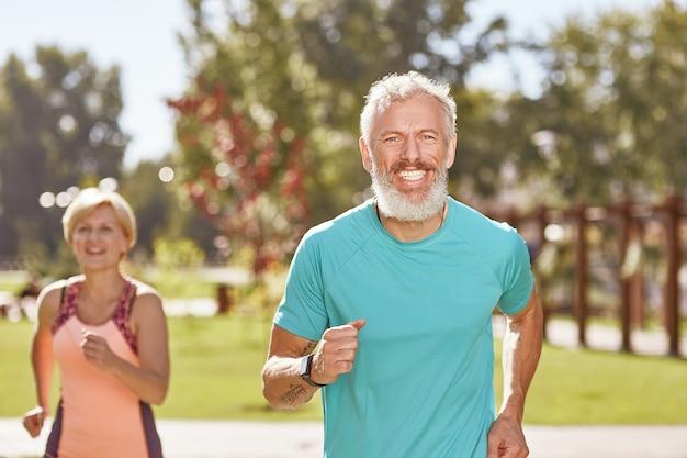 Оставаясь здоровым и подтянутым, счастливый зрелый мужчина улыбается в камеру во время бега вместе со своей женой в