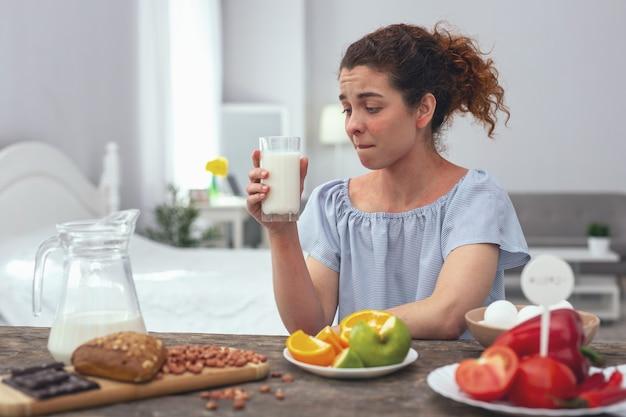 健康を保つ。夕食のテーブルに座って、毎日コップ一杯のミルクを飲むことによってカルシウムの彼女の毎日の比率を消費しようとしている若い女の子