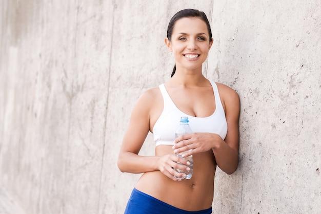 水分補給を続けます。水でボトルを保持し、コンクリートの壁に寄りかかって笑っているスポーツ服の美しい若い笑顔の女性